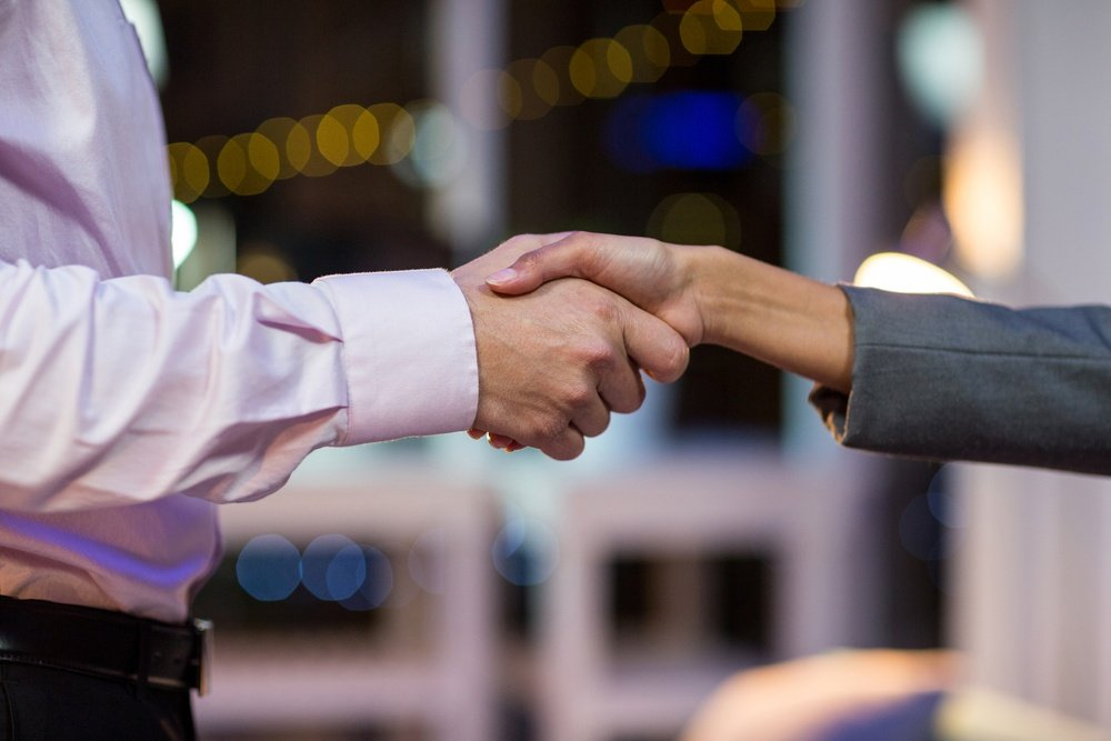Close-up of businesspeople shaking hands in office at night.jpeg