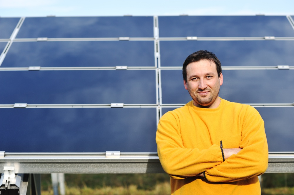 Young male engineer with solar panels in background.jpeg
